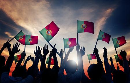 personas saludando: Grupo de personas que ondeaban banderas portuguesas en Contraluz