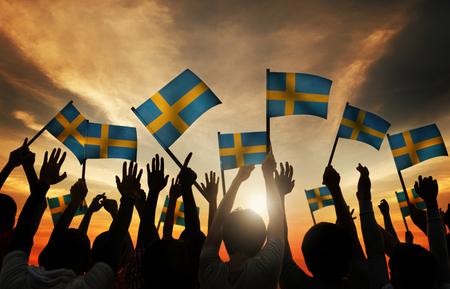 personas saludando: Grupo de personas que ondeaban banderas suecas en Contraluz Foto de archivo