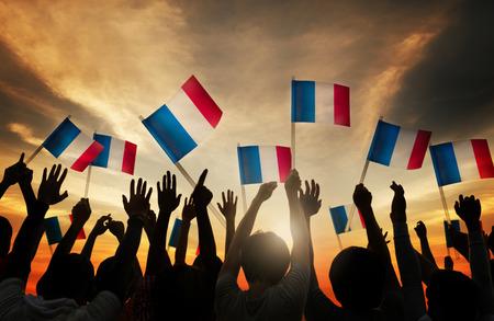 personas saludando: Grupo de personas que ondeaban banderas francesas en Contraluz