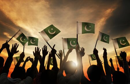 gente saludando: Grupo de personas que ondeaban la bandera de Pakist�n en Contraluz Foto de archivo
