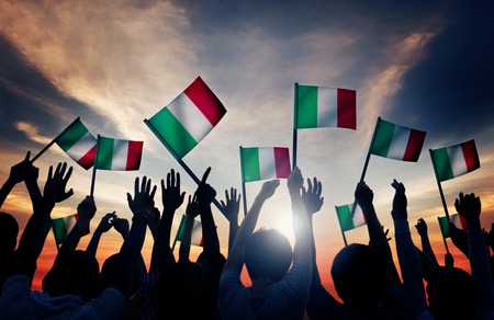 personas saludando: Grupo de personas que ondeaban banderas italianas en Contraluz Foto de archivo