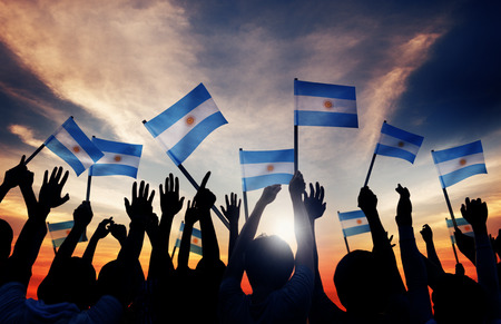 bandera argentina: Siluetas de personas que tienen la bandera de Argentina Foto de archivo