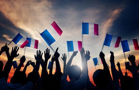 Groep Mensen Zwaaien Franse Vlaggen in Tegenlicht Stockfoto