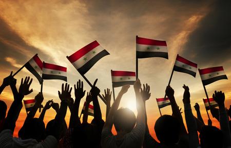 personas saludando: Grupo de personas que ondeaban la bandera de Siria en Contraluz