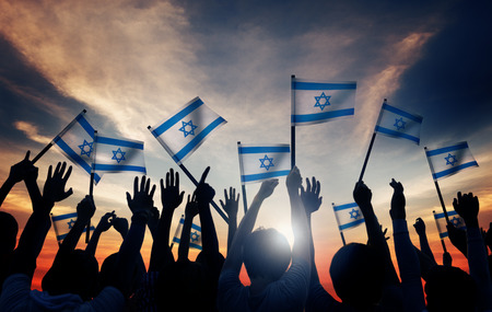 israel people: Silhouettes of People Holding Flag of Israel Stock Photo