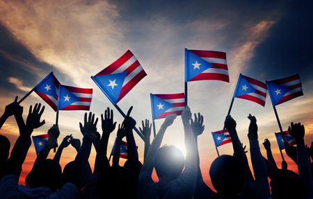 Group of People Waving Flag of Puerto Rico in Back Lit Stock Photo