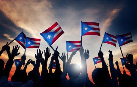 personas saludando: Grupo de personas que ondeaban la bandera de Puerto Rico en Contraluz