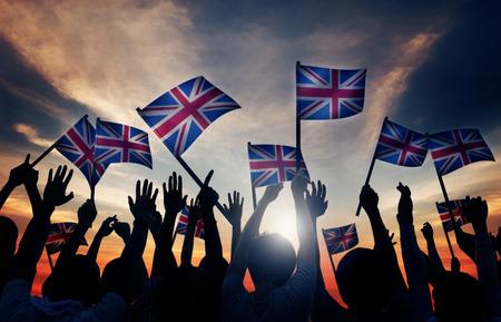 gente saludando: Grupo de personas que ondeaban banderas del Reino Unido en Contraluz Foto de archivo