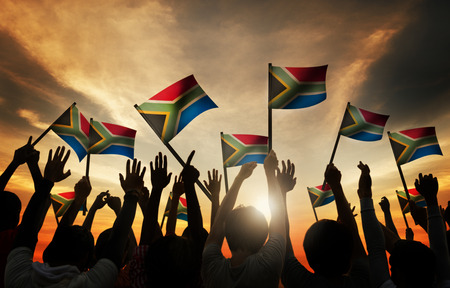 personas saludando: Grupo de personas que ondeaban banderas sudafricanas en Contraluz Foto de archivo