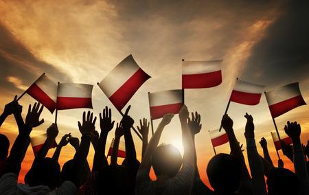 gente saludando: Grupo de personas que ondeaban banderas polacas en Contraluz