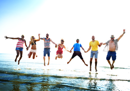people group: Diverse Beach Summer Friends Fun Jump Shot Concept Stock Photo