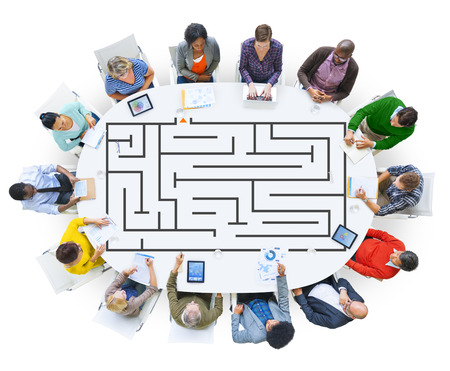People brainstorming on a table with a maze