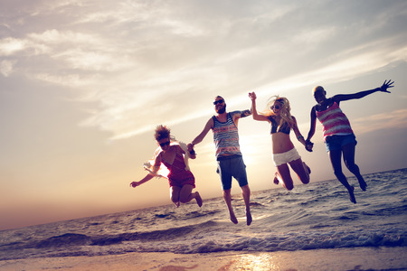 enjoy: Diverse Beach Summer Friends Fun Jump Shot Concept Stock Photo