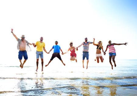 Diverse Beach Summer Friends Fun Jump Shot Concept 版權商用圖片