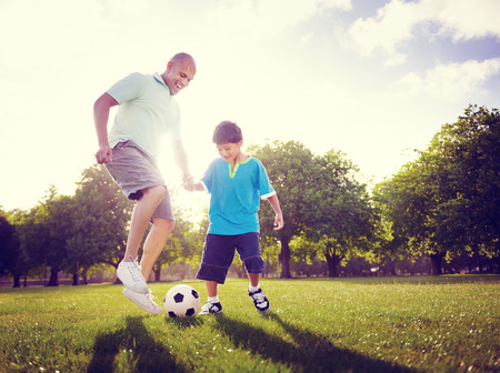 family on grass: Family Father Son Playing Football Summer Concept Stock Photo