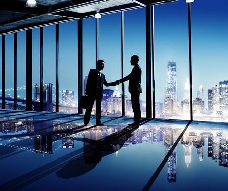 2 Multikulturelle Geschäftsleute Händeschütteln mit Innenstadt Als Hintergrund Standard-Bild