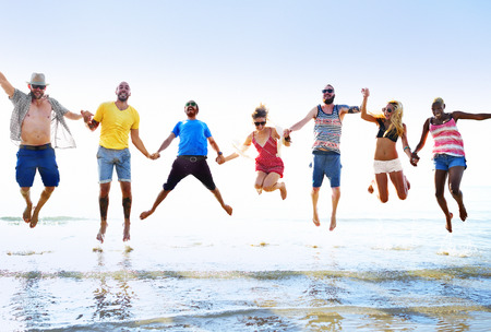 young adults: Diverse Beach Summer Friends Fun Jump Shot Concept Stock Photo