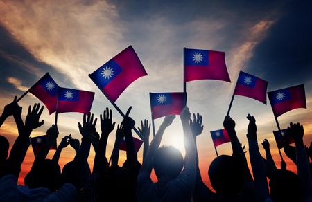 personas saludando: Grupo de personas que ondeaban banderas taiwanesas en Contraluz Foto de archivo