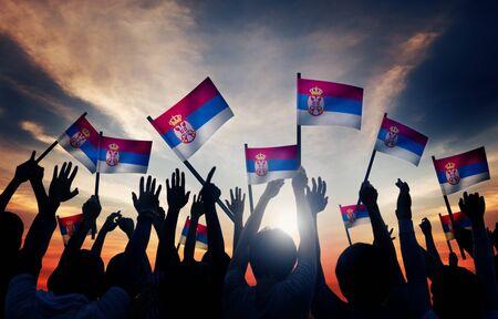personas saludando: Grupo de personas que ondeaban la bandera de Serbia en Contraluz Foto de archivo