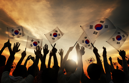 Silhouettes of People Holding Flag of South Korea Imagens