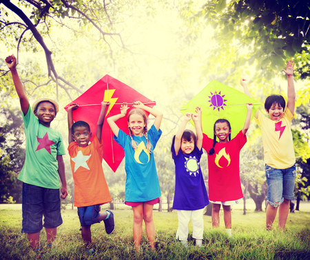 kids activities: Children Flying Kite Playful Friendship Concept Stock Photo