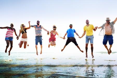 fun: Diverse Beach Summer Friends Fun Jump Shot Concept Stock Photo