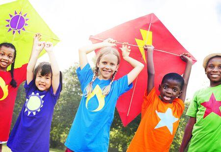 flying kite: Children Flying Kite Playful Friendship Concept Stock Photo
