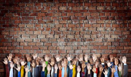 diverse hands: Group of Diverse Hands Raised on Brick Wall
