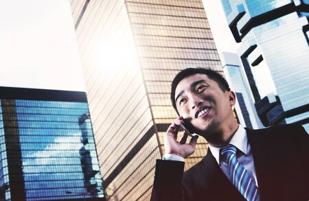 young adult men: Businessman China Hong Kong Talking Phone Concept Stock Photo