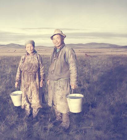herder: Mongolian Couple Farmers Holding Basin Posing Field Concept Stock Photo
