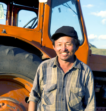 mongolian: Smiling Mongolian Farmer Standing Next Tractor Concept Stock Photo
