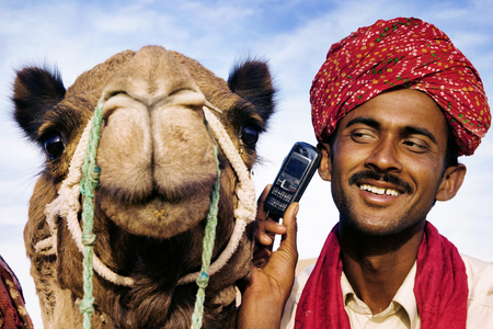 indian animal: Asian Man and Camel in the Desert with Communications Concept