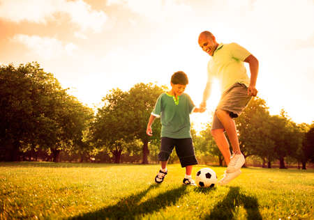preadolescent: Little boy playing soccer with his father Concept