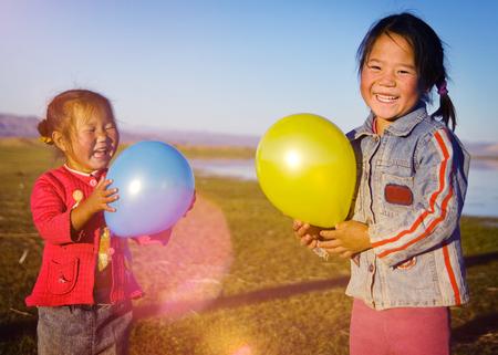 mongolian: Asian Girls Playing Lake Balloon Rural Mongolian Concept