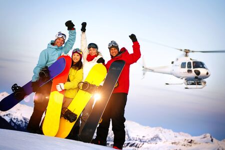 skiing: Snowboarders on Top of the Mountain with Heli Ski Concept Stock Photo