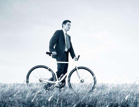 empujando: El hombre de negocios que empuja la bici al aire libre Concepto Foto de archivo