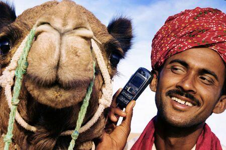 camello: Asia Hombre y camello en el desierto con Concept Comunicaciones Foto de archivo