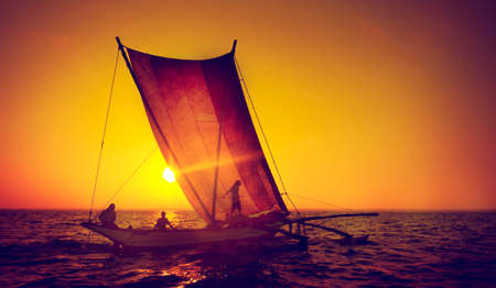 catamaran: Fishermen on a catamaran at Sunset Concept