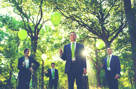 woman standing: Group of business people holding balloons in the forest