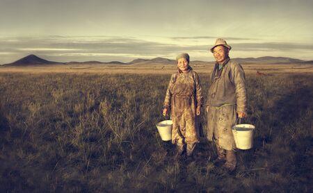 mongolian: Mongolian Couple Farmers Holding Basin Posing Field Concept Stock Photo