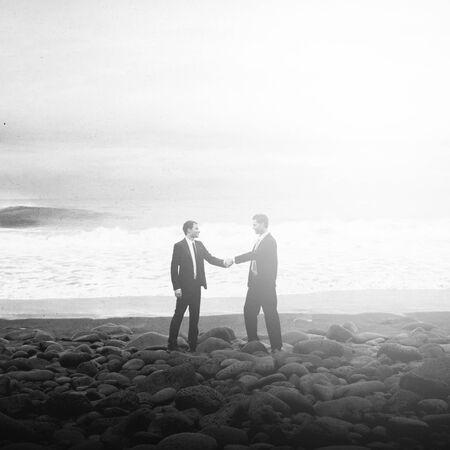 personas saludandose: Los hombres de negocios que sacuden las manos Beach Acuerdo Corporativo Concepto Foto de archivo