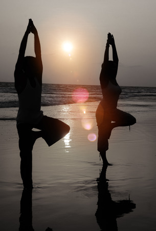 serene people: Serene People In The Beach Doing Yoga In The Sunset Concept