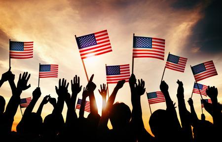 personas saludando: Grupo de personas que ondeaban banderas americanas en Contraluz