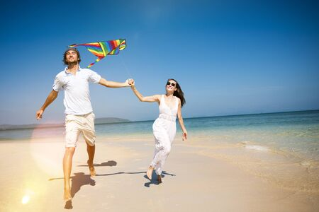 away from it all: Playing Kite Couple Relaxing Beach Carrying Summer Concept Stock Photo