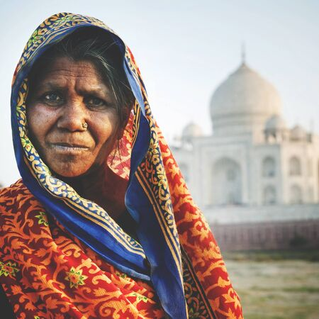 woman standing: Indigenous Indian Woman And Taj Mahal Backgroud Concept