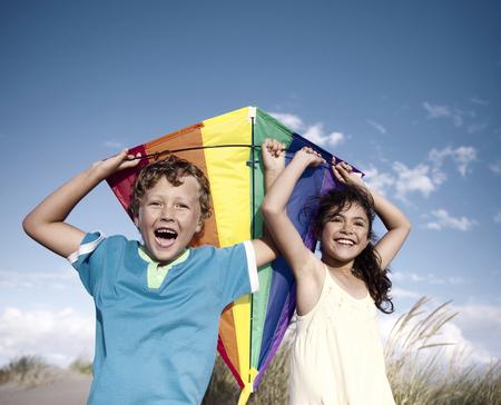 papalote: Niños alegres que juegan Kite Aire libre Concepto