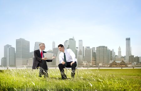 persuading: Two Business Men Discussion Documents Outdoors Concept