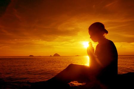 Junge Frau beten Sonnenuntergang über dem Ozean Konzept Standard-Bild - 46948765