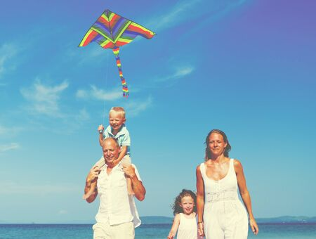 away from it all: Family Beach Holiday Flying Kite Sea Togetherness Concept