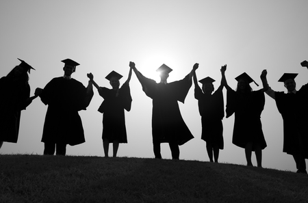 hands raised: Group Students Hands Raised Graduation Silhouette Concept Stock Photo